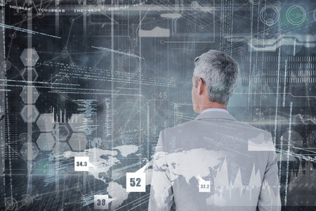 thirties: Rear view of businessman standing hands in pockets against hologram background Stock Photo