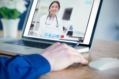 medical student: Businessman using laptop in office against pretty medical student smiling at camera Stock Photo