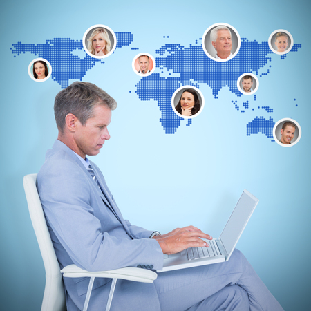 swivel chair: Handsome businessman sitting on a swivel chair and using his laptop against blue background