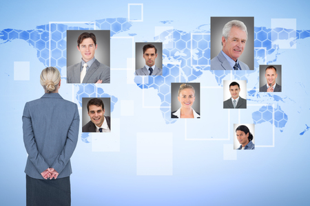 hands behind back: Businesswoman standing with hands behind back against background with world map Stock Photo