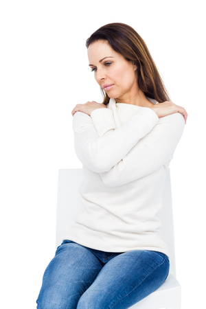 wistfulness: Desperate woman crossing arms on shoulders on white background