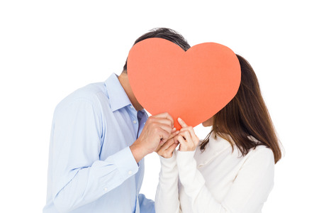 big behind: Lovely couple kissing behind big heart on white background