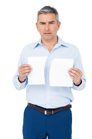 strife: Stern man holding ripped paper on white background