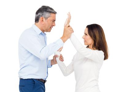 grabbing: Violent man grabbing wifes wrists against white background