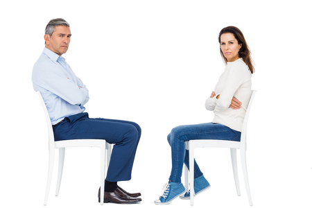 strife: Couple arguing while sitting against white background
