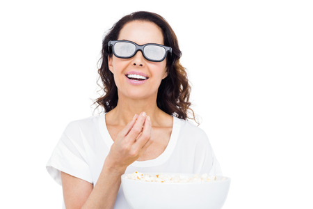3d: Pretty woman with 3D glasses eating popcorn over white background Stock Photo