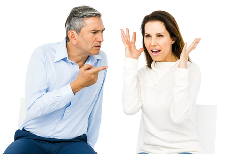 pareja discutiendo: Couple arguing while sitting against white background