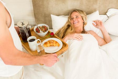 spoiling: Cute man bringing breakfast to his girlfriend in bed