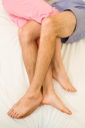 legs around: Close up of couple legs around each other in their bed
