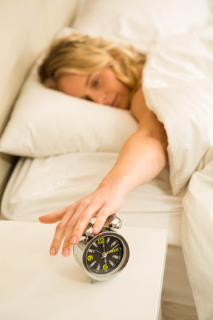 shutting: Pretty woman shutting off her alarm clock in the bedroom