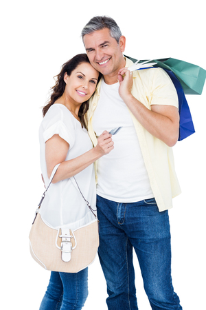 Portrait of happy couple with shopping bags and credit card against white background Stock Photo