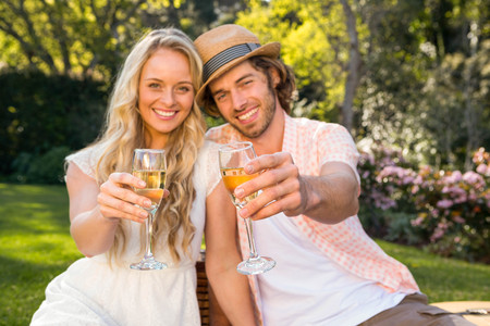 al fresco: Happy couple having a picnic and drink champagne in the garden Stock Photo