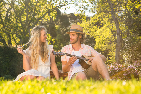 al fresco: Happy couple having a picnic and playing guitar in the garden Stock Photo