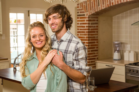 arms around: Cute couple hugging with arms around in the kitchen