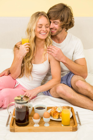 spoiling: Cute couple having breakfast sitting on their bed in the bedroom