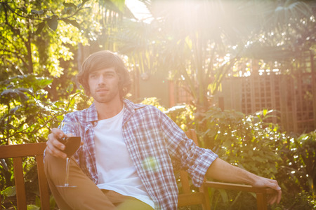 weekend activity: Man sitting on a bench with a glass of red wine in the garden