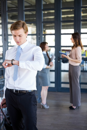 checking time: Successful businessman checking time while his colleagues interacting with each other in background Stock Photo