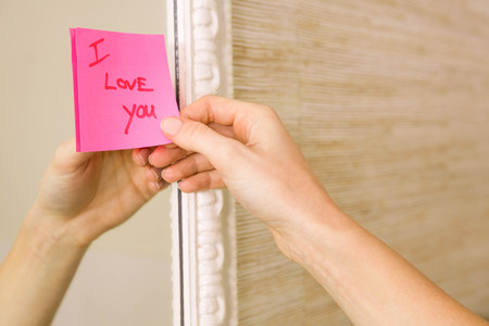 sticking to: Woman sticking I love you word sticky note on mirror Stock Photo