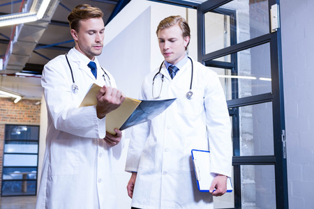 medical report: Doctors discussing a medical report in hospital Stock Photo