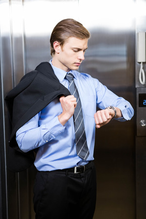 checking time: Businessman checking time while waiting for elevator in office