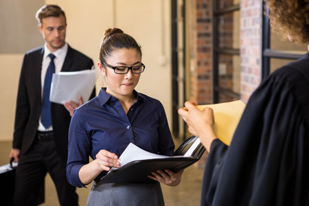 interacting: Lawyer looking at documents and interacting with businesswoman in office