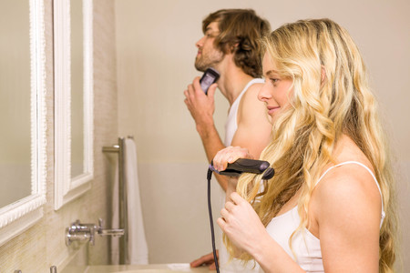 straightener: Cute couple using a razor and a straightener in the bathroom at home