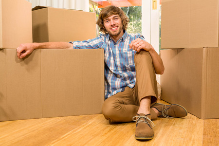 unpack: Handsome man posing with moving boxes in his new house