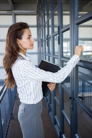 knocking: Young businesswoman knocking office door