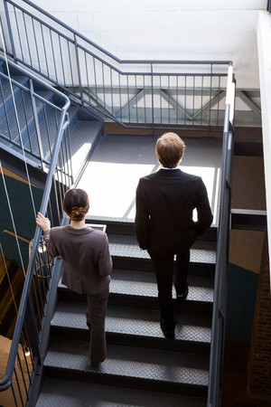 well dressed: Two well dressed businesspeople climbing the staircase of the office