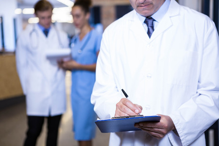 doctor writing: Male doctor writing on clipboard in hospital Stock Photo