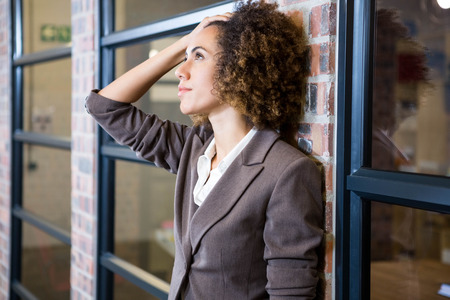 hand on forehead: Frustrated businesswoman with hand on forehead in office Stock Photo