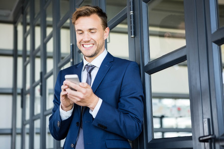 text messaging: Businessman text messaging on smartphone in office Stock Photo