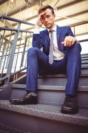 worried businessman: Worried businessman sitting on stairs in office