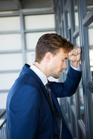 tired businessman: Tired businessman leaning on door in office
