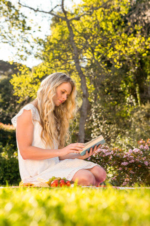 weekend activity: Beautiful blonde sitting on the grass reading in the garden