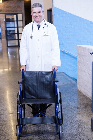 wheel chair: Portrait of male doctor standing with wheel chair in hospital Stock Photo