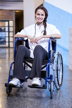 wheel chair: Portrait of happy female doctor sitting on wheel chair in hospital Stock Photo