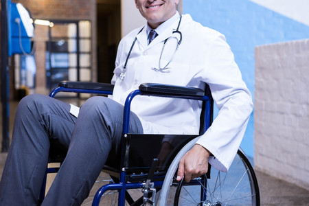 wheel chair: Male doctor sitting on wheel chair in hospital