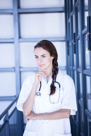 health professional: Thoughtful female doctor standing with hand on chin in hospital Stock Photo