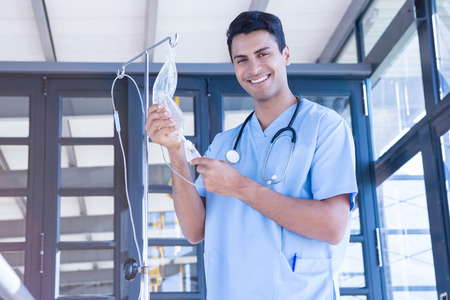 an intravenous drip: Portrait of doctor holding intravenous drip in hospital