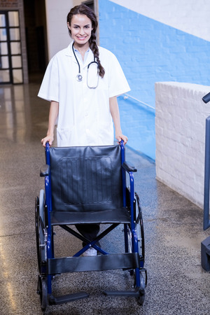 wheel chair: Portrait of female doctor standing with wheel chair in hospital