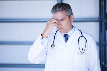 tensed: Tensed doctor standing with hand on forehead in hospital Stock Photo