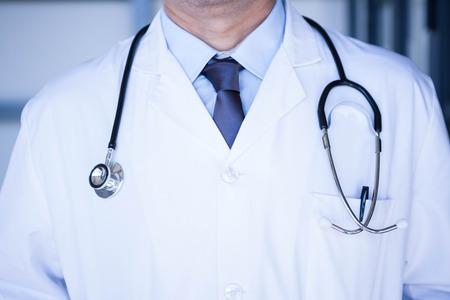 bata de laboratorio: Mediados de sección de médico en bata de laboratorio usando el estetoscopio alrededor del cuello en el hospital