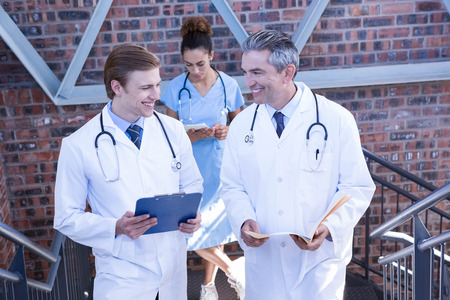 medical report: Doctors discussing medical report on staircase in hospital Stock Photo