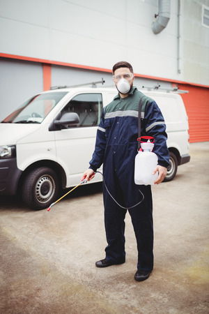 insecticide: Handyman with insecticide standing in front of his van