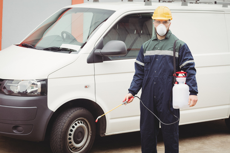 pest control: Handyman with insecticide standing in front of his van
