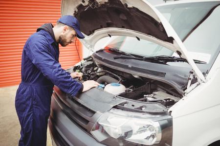 engine bonnet: Mechanic fixing the engine of a van Stock Photo