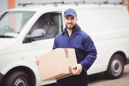 distribution box: Delivery man holding box in front of his van