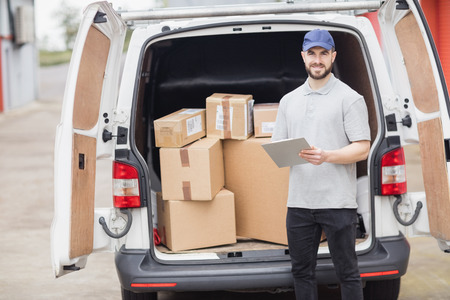 loading bay: Delivery man holding clipboard in front of his van