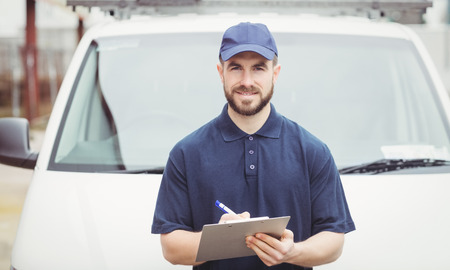 loading bay: Delivery man writing on clipboard in front of his van Stock Photo